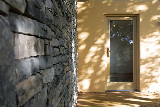 The contrasting finishes of the Aquapanel clad extension and stone outbuilding